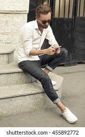 Young stylish man sitting on steps and reads text on  phone. Lifestyle.