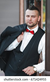 Young stylish man in a suit. Portrait of the groom. The groom is holding his jacket  on his shoulder, look at the camera. Hand with golden watch. Business concept.