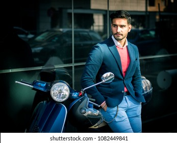 Young stylish man in suit and sunglasses standing by his classic Italian scooter on empty road in sunny city.