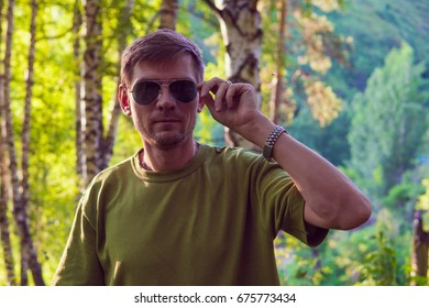 Young stylish man in summer forest in the mountains near Almaty city.