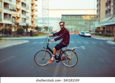 Young stylish man in sunglasses riding a bike on city street