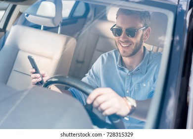 young stylish man in sunglasses using smartphone while driving car