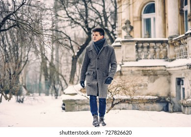 Young stylish man in warm gray coat and leather gloves walking down the snowy street. Street style.