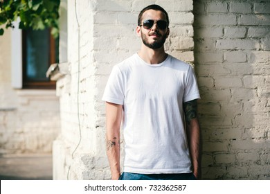 Young stylish man wearing white blank design t-shirt with beard in glasses, standing on the street on city background. Street photo