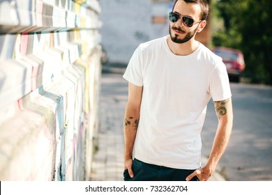 Young stylish man wearing white blank t-shirt with beard in glasses, standing on the street on city background. Street photo