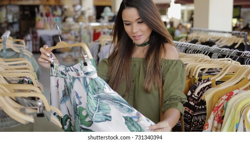 Young stylish model in casual dress standing in clothing shop and exploring beautiful dress on hangers while shopping alone.