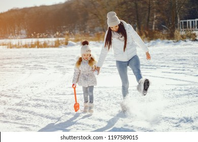 young and stylish mom with long dark hair playing with her little cute daughter in winter snow park