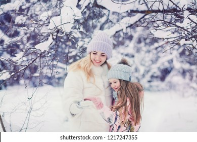 young and stylish mom playing with her little cute daughter in winter snow park