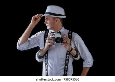Young stylish photographer with retro camera over black background