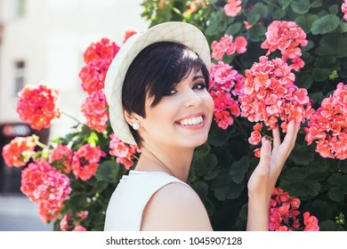 Young stylish plus size model in dark blue dress posing near the flower bush on the city street. Cute woman with short dark hair smiling near the flowers