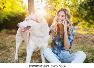 young stylish pretty smiling blond woman playing with dog in park, happy, husky breed, summer style, sunny, positive mood, talking on phone, communication