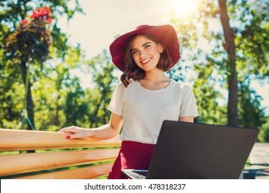 young stylish pretty woman using laptop outside