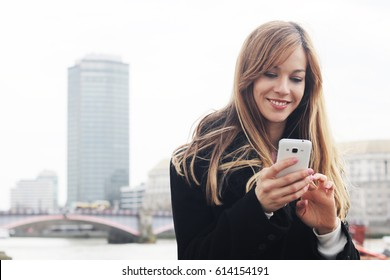 Young stylish pretty woman using smart phone app on London city bridge, thames and skyscraper background. Londoner executive lifestyle in England, Great Britain, UK, United kingdom. Vacation europe