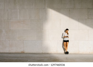 Young stylish professional woman taking a break for texting on smartphone.