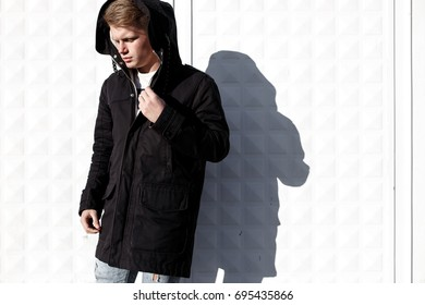 Young stylish redhead man in trendy outfit posing against urban background