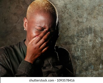 young stylish sad and depressed afro american black woman crying in despair covering face with hands feeling miserable and desperate suffering depression in dramatic facial expression isolated