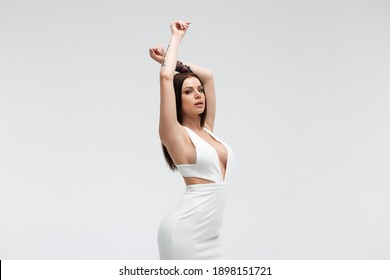 Young stylish seductive female in trendy white dress with low neckline looking erotically at camera