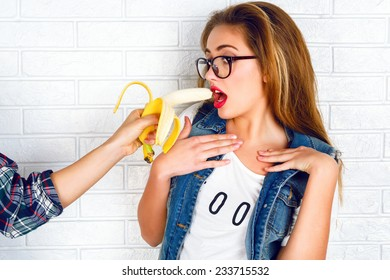 Young stylish sexy pretty hipster girl having fun, and surprised. Funny image of man hand feeds with big banana blonde woman.