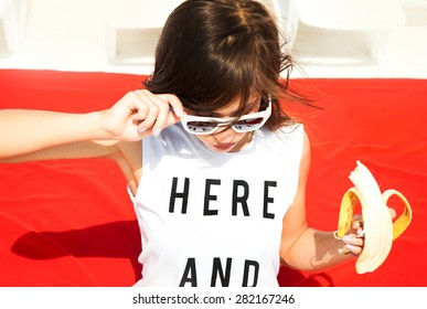 Young stylish sexy pretty hipster girl having fun, on the beach,and eating fruits. Funny image of  woman eating big banana and having fun.Sunshine sunglasses,Hare and now