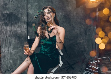 young stylish sexy woman on cinema backstage, celebrating with a glass of champagne, green velvet evening dress, party mood, luxury style, fashion trend, holding carnival mask