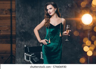 young stylish sexy woman on cinema backstage, celebrating with a glass of champagne, green velvet evening dress, party mood, luxury style, fashion trend,