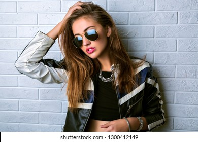 Young stylish sexy woman posing near brick white wall, police cosplay style, wearing leather jacket, glasses, crop top and trendy jewelry, grunge rock style.