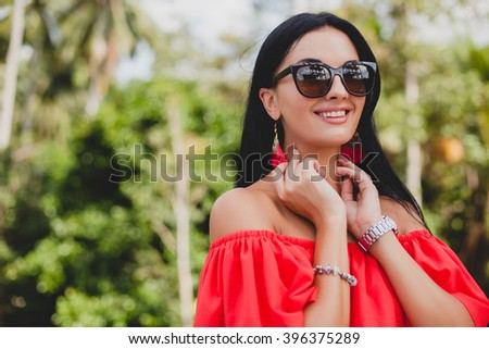 young stylish sexy woman in red summer dress standing on terrace in tropical hotel, palm trees background, long black hair, sunglasses, ethnic earrings, sunglasses, looking forward, smiling, close up