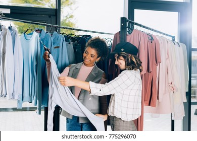 young stylish shopping buddies looking at new shirt in clothing store