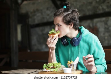 A young stylish teenager with curved hair and with earphones eating a burger and French fries in cafe over background, street and fast food concept