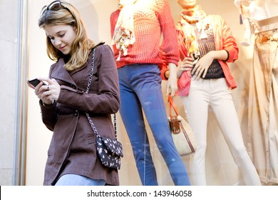 Young stylish teenager woman using a smartphone device while visiting the city, leaning on a fashion store shop window while shopping for clothes.