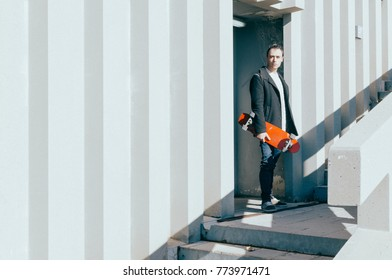 young stylish urban man walks out of a building with a red skateboard in his hand on a sunny day