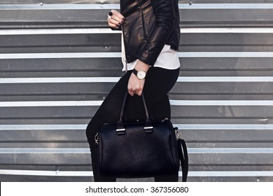 Young stylish woman in black trendy outfit with big bag in hand street look