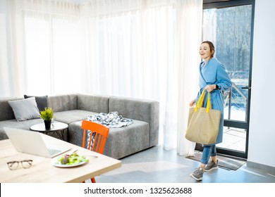 Young stylish woman in blue coat coming home with shopping back, entering the door of the modern apartment