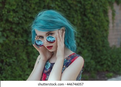 Young and stylish woman with blue hair and red lips touching her sunglasses beside to nature background
