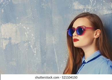 Young stylish woman in blue shirt and sunglasses on grey background