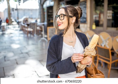 Young stylish woman buying a french baguette standing on the street in Lyon city