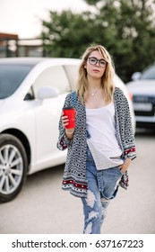 Young stylish woman in a city street near a white car.