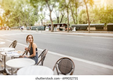 Young stylish woman drinking coffee outdoors at the cafe in Paris. Wide angle view with copy space