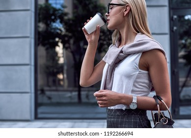 Young stylish woman drinks her morning coffee. Confident businesswoman in stylish casual wear looks at shop windows and holding coffee to go