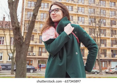 Young stylish woman in eyeglasses with red handbag in the city. Smiling girl in dark green coat walking on the streets. Street fashion look