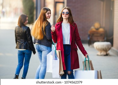 Young stylish woman in fashionable trench coat and sunglasses walking in the street with many paper bags. Shopping, sale, consumerism and people concept