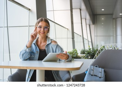 Young stylish woman in glasses sits at a table in a cafe and holds a tablet in her hands.