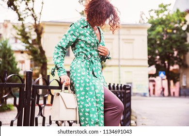 Young stylish woman in green coat with leather white handbag in hands. Fashionable woman in green cotton dress. Street fashion look