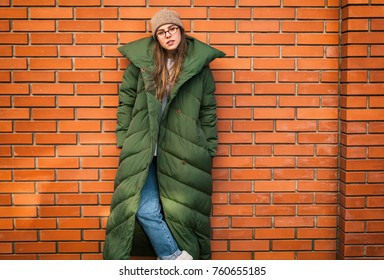 Young stylish woman in a green down jacket on city street by the