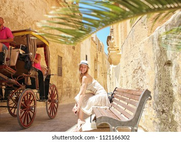 Young stylish woman in hat traveling in the Mdina city, Malta 2018