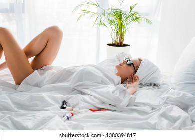 young stylish woman in jewelry and sunglasses with towel on head lying in bed with nail polishes