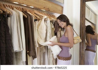 Young stylish woman looking at clothes in fashion store.