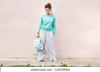 Young stylish woman in mint green hoody with leather blue backpack. Fashionable sport woman in green and gray cotton suit. Casual street fashion look