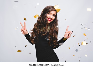 Young stylish woman on white background drinking champagne, celebrating new year, wearing black dress and yellow crown, happy carnival disco party, sparkling confetti, holding glass, having fun