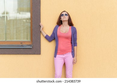 Young stylish woman posing against the wall.